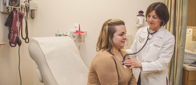 Faculty member Marianne Davies examines a patient at Smilow Cancer Hospital.
