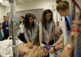 Students giving CPR to a simulation manikin.